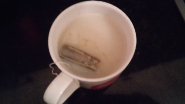 Tea bag in a mug of milky tea
