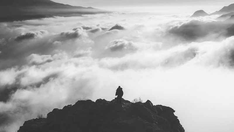 Photo of a person on a mountain top surrounded by clouds by Cristina Gottardi on Unsplash